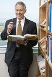 Lächelnder älterer Geschäftsmann in der Bibliothek Stockfotografie