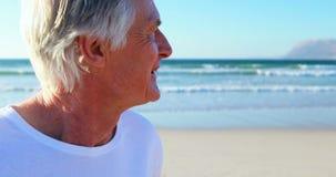 Lächelnder älterer Mann, der auf Strand steht stock video