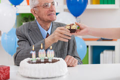 Lächelnder älterer Mann, der Geburtstagsgeschenk empfängt Stockbild