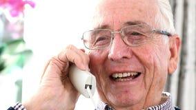 Lächelnder älterer Mann, der zu Hause auf Telefon-Lektion spricht stock video footage