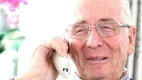 Lächelnder älterer Mann, der zu Hause am Telefon spricht stock footage