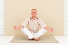 Lächelnder älterer Mann des beiläufigen Geschäftsyoga meditieren Stockbild