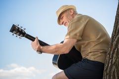 Lächelnder älterer Mann im Hut, der am Baum und am Spielen der Gitarre sich lehnt Lizenzfreies Stockbild