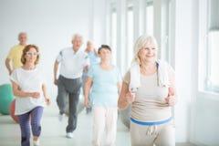 Lächelnder älterer Trainer, der Übung zeigt lizenzfreie stockbilder