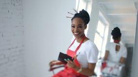 Lächelnder afrikanischer Kosmetiker des Positivs hält den Satz von Bürsten und spinnt auf den Stuhl nahe dem enormen Spiegel here stock video footage