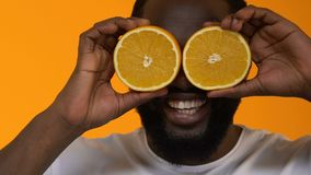 Lächelnder afrikanischer Mann, der saftige orange Hälftefront von Augen, Vitamin C, Diät zeigt stock video