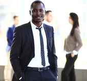 Lächelnder AfroamerikanerGeschäftsmann mit den Führungskräften, die im Hintergrund arbeiten Stockfoto