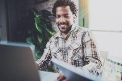 Lächelnder Afroamerikanermann, der Laptop beim Sitzen im Wohnzimmer verwendet Konzept der jungen Kerlanwendung internetfähig stockfoto