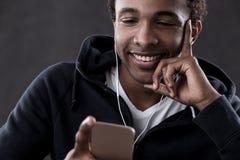 Lächelnder Afroamerikanermann, der Telefonschirm betrachtet Stockbilder