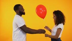 Lächelnder afroer-amerikanisch Mann, der Ballon netter Frau, Geburtstagsgeschenk, Datum darstellt stock video footage