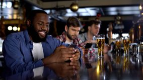 Lächelnder afroer-amerikanisch Mann, der in der Kneipe schaut durch die Datierung von Standortsucht sitzt stockfotos