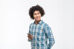 Lächelnder afroer-amerikanisch Mann, der Smartphone hält stockfotos
