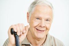 Lächelnder alter Mann mit Stock Stockfoto