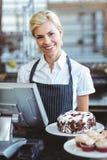 Lächelnder Angestellter, der Taschenrechner auf Zähler verwendet Stockfoto