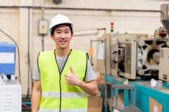 Lächelnder Arbeiter mit Sicherheit stark in den industriellen Anlagen mit den Daumen oben stockfoto
