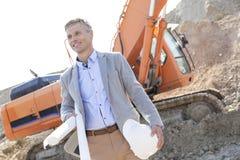 Lächelnder Architekt, der beim Halten von Plänen und von Hardhat Baustelle weg betrachtet Stockfotos