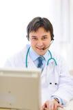 Lächelnder Arzt mit dem Kopfhörer, der an PC arbeitet Lizenzfreies Stockbild