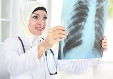 Lächelnder asiatischer Arzt, der Röntgenstrahl betrachtet Lizenzfreie Stockfotografie
