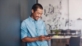 Lächelnder asiatischer Designer, der eine Tablette in einem modernen Büro verwendet stockfotografie