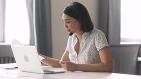 Lächelnder asiatischer Geschäftsfrau-Abnutzungskopfhörer, der Laptop betrachtend spricht stock footage