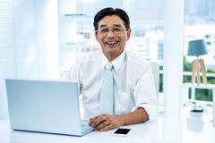 Lächelnder asiatischer Geschäftsmann, der an Laptop arbeitet Stockbilder