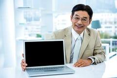 Lächelnder asiatischer Geschäftsmann, der seinen Laptop zeigt Stockfotografie