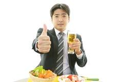 Lächelnder asiatischer Geschäftsmann mit Bier Stockfoto