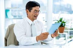 Lächelnder asiatischer Geschäftsmann unter Verwendung der Tablette Stockfoto