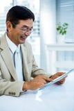 Lächelnder asiatischer Geschäftsmann unter Verwendung der Tablette Lizenzfreie Stockbilder