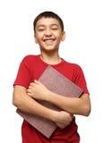 Lächelnder asiatischer Junge, der großes Buch anhält Stockbilder