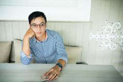 Lächelnder asiatischer Mann im zufälligen gekleideten Ausarbeiten des Büros während stockfotografie