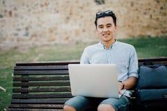 Lächelnder asiatischer Mann mit dem Laptopnotizbuch, das auf Bank im s sitzt lizenzfreies stockfoto