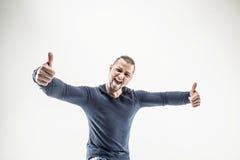 Lächelnder athletischer Kerlbodybuilder in den Jeans und in T-Shirt, die Th zeigen Lizenzfreie Stockbilder