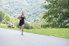 Lächelnder athletischer Mann, der in den Park läuft Stockfotografie
