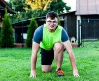Lächelnder athletischer Mann, der für einen Morgenstoß um die Gemeinschaft sich vorbereitet Ein Kerl, der Bein und Arm auf den gr lizenzfreie stockbilder