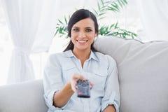 Lächelnder attraktiver Brunette, der Fernsehkanäle ändert Lizenzfreie Stockbilder