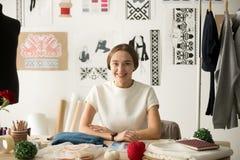 Lächelnder attraktiver Modedesigner, der am Arbeitsplatzschauen sitzt lizenzfreie stockbilder