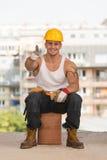 Lächelnder Auftragnehmer, der sich Daumen zeigt Lizenzfreie Stockfotografie