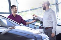 Lächelnder Autohändler, der dem neuen Käufer in einem behandelnden Salon Schlüssel gibt stockfotos