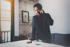 Lächelnder bärtiger afrikanischer Mann, der auf Smartphone bei der Stellung des nahen Holztischs in seinem modernen Haus spricht  stockbild