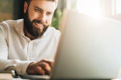 Lächelnder bärtiger Geschäftsmann der Junge, der bei Tisch im Büro, unter Verwendung des Laptops sitzt Mann arbeitet an Computer, Lizenzfreies Stockbild