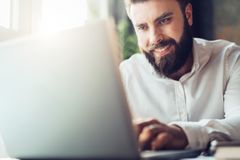 Lächelnder bärtiger Geschäftsmann der Junge, der bei Tisch im Büro, unter Verwendung des Laptops sitzt Mann arbeitet an Computer, Stockfotos