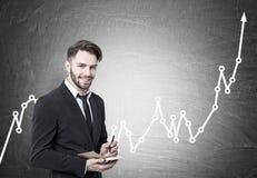 Lächelnder bärtiger Geschäftsmann, steigendes Diagramm Lizenzfreies Stockfoto