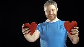 Lächelnder bärtiger Mann im blauen T-Shirt hält zwei rote Herzformen Lieben Sie, Romance, Datierung, Verhältnis-Konzepte schwarze Lizenzfreies Stockbild