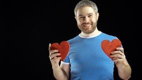 Lächelnder bärtiger Mann im blauen T-Shirt hält zwei rote Herzformen Lieben Sie, Romance, Datierung, Verhältnis-Konzepte schwarze stock footage