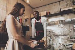 Lächelnder barista Mann erteilt einem Mädchen ihren Auftrag lizenzfreies stockbild