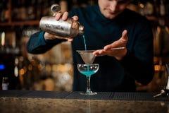 Lächelnder Barmixer, der neues Getränk mit blauem Alkohol von einem Schüttel-Apparat in ein Glas unter Verwendung des Siebs gießt Lizenzfreie Stockfotografie