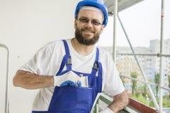 Lächelnder Bauarbeiter in einer Arbeitsausstattung, in Schutzhandschuhen und in einem Sturzhelm auf seinem Kopf zieht eine silber Stockfoto