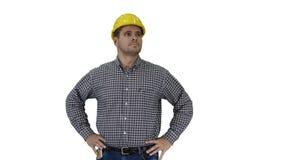 Lächelnder Bauarbeiter im gelben Sturzhelm, der perfekte gut gebaut Gegenstand Hände auf Hüften auf weißem Hintergrund betrachtet stock footage