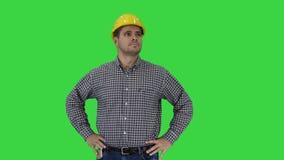 Lächelnder Bauarbeiter im gelben Sturzhelm, der perfekte gut gebaut Gegenstandhände auf Hüften auf einem grünen Schirm betrachtet stock video footage